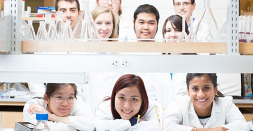 students standing behind a desk full of lab equipment